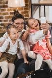 de gelukkige familie die van de jaren '50stijl selfie met smartphone nemen stock fotografie