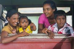 De gelukkige familie die van Sri Lanka uit het treinvenster kijken Stock Foto's