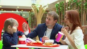 De gelukkige familie eet in snel voedselkoffie in wandelgalerij De familie heeft diner in snel voedsel Een onderbreking tussen he stock footage