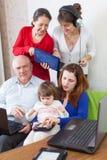De gelukkige familie gebruikt diverse elektronische apparaten in huis royalty-vrije stock afbeelding