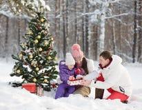 De gelukkige familie geeft giften in de winterbos stock foto's