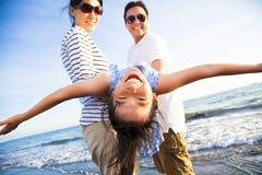 De gelukkige familie geniet de zomer van vakantie op het strand Stock Afbeelding