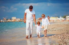 De gelukkige familie geniet de zomer van vakantie op azuurblauwe kust, samen lopend in de branding Stock Afbeelding