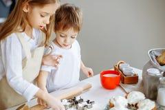 De gelukkige familie grappige jonge geitjes bereiden het deeg voor, bakken koekjes in de keuken royalty-vrije stock fotografie