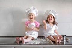 De gelukkige familie grappige jonge geitjes bereiden het deeg voor, bakken koekjes in de keuken Stock Afbeeldingen