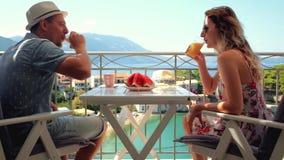 De gelukkige familie heeft een ontbijtzitting op balkon bij mooie eilandachtergrond stock video