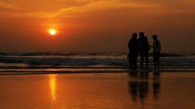 De gelukkige familie heeft pret en het letten op zonsondergang op het strand stock footage