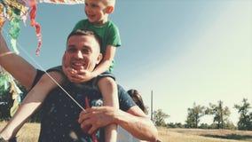 De gelukkige familie, het mamma, de papa en de zoon lopen in aard, lancerend een luchtslang Voorraadlengte stock videobeelden