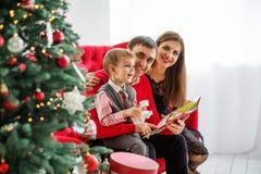 De gelukkige familie leest een boek dichtbij een Kerstboom Stock Fotografie