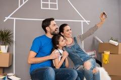 De gelukkige familie maakt binnenshuis selfie die voor verkoop is Concept 6 van onroerende goederen Concept huis het verkopen royalty-vrije stock afbeelding