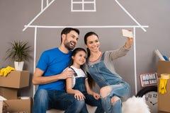 De gelukkige familie maakt binnenshuis selfie die voor verkoop is Concept 6 van onroerende goederen Concept huis het verkopen stock afbeelding