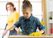 De gelukkige familie maakt ruimte schoon De moeder en haar kinddochter doen binnenshuis het schoonmaken Vrouw en weinig jong geit stock afbeelding