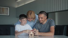 De gelukkige familie, mamma, vader en zoonszitting bij de lijst verzamelt houten model van het huis Het schaak stelt bischoppen v stock video