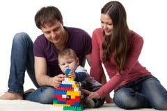 De gelukkige familie met baby bouwt huis. Stock Afbeeldingen