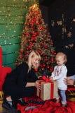 De gelukkige familie met een kind viert het nieuwe jaar dichtbij de Kerstboom stock foto