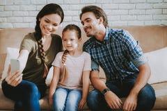 De gelukkige Familie met Meisje in Flat maakt Selfie stock foto's