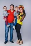 De gelukkige familie met twee kleine jongens in de herfstfamilie kijkt Stock Afbeeldingen