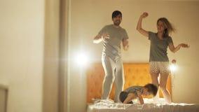 De gelukkige familie met weinig zoon die en heeft pret thuis op bed in de avond vóór bedtijd dansen stock videobeelden