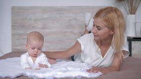 De gelukkige familie, nieuwe jonge moeder met haar pasgeboren dochter die op bed liggen en kijkt in camera stock videobeelden