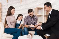 De gelukkige familie ondertekent partnerovereenkomst om huis samen met makelaar in onroerend goed te kopen stock foto's