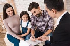 De gelukkige familie ondertekent partnerovereenkomst om huis samen met makelaar in onroerend goed te kopen royalty-vrije stock foto's