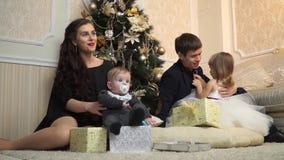 De gelukkige familie ontleedt giften dichtbij een Kerstboom stock video
