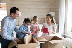 De gelukkige familie pakt kartondozen uit die zich aan nieuw huis bewegen stock afbeelding