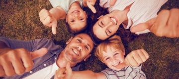 De gelukkige familie in park die samen beduimelt omhoog gesturing royalty-vrije stock fotografie