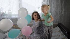 De gelukkige familie speelt in het bed die thuis pyjamapartij worden De oudere zuster houdt een buhch van kleurrijke lucht stock video