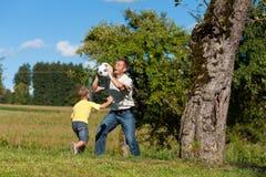De gelukkige familie speelt voetbal in de zomer royalty-vrije stock fotografie