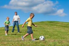De gelukkige familie speelt voetbal in de zomer stock afbeelding