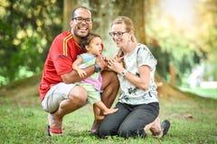 De gelukkige familie tussen verschillende rassen geniet van een dag in het park Stock Fotografie