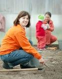 De gelukkige familie zaait zaden in grond Royalty-vrije Stock Afbeelding