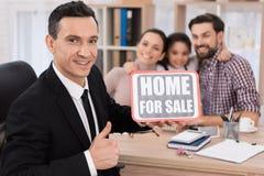 De gelukkige familie zit bij lijst van makelaar in onroerend goed die teken met inschrijving houdt Huis voor Verkoop stock foto's