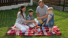 De gelukkige familie zit op deken en de vader giet jus d'orange stock videobeelden