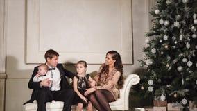 De gelukkige familie zit op een bank in Kerstmisvooravond in zaal met verfraaide sparren stock videobeelden
