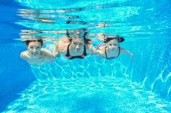 De gelukkige familie zwemt onderwater in pool Stock Foto's