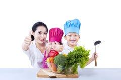 De gelukkige familiechef-kok bereidt vegetarische maaltijd op wit voor Stock Fotografie