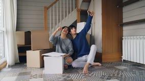 De gelukkige de familieechtgenoot en vrouw nemen selfie met huissleutels zittend op vloer van nieuwe flat dichtbij kartondozen me stock footage