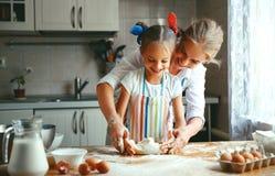 De gelukkige de familiemoeder en dochter bakken het kneden deeg in keuken royalty-vrije stock fotografie