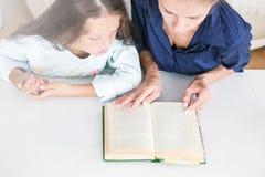 De gelukkige de familiemoeder en dochter lezen een boek thuis in de avond  stock afbeelding