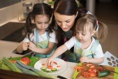 De gelukkige de familiemoeder en jonge geitjes bereiden gezond voedsel voor, maken zij grappig gezicht met groentenhap in de keuk royalty-vrije stock afbeelding