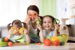 De gelukkige de familiemoeder en jonge geitjes die pret met voedselgroenten hebben bij keuken houden peper vóór hun ogen als in g stock afbeeldingen
