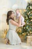 De gelukkige familiemoeder en jongen van de kindbaby op Kerstmisochtend bij de boom met giften, huisdecoratie, binnenlands huis Stock Afbeelding