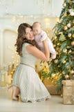 De gelukkige familiemoeder en jongen van de kindbaby op Kerstmisochtend bij de boom met giften, huisdecoratie, binnenlands huis Stock Foto