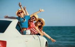 De gelukkige familiemoeder en de kinderenmeisjes gaan naar de reis van de de zomerreis in auto stock foto