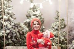 De gelukkige familiemoeder en de kindjongen in santahoed dichtbij sneeuw behandelden Kerstbomen met het zitten op schommeling Hel Stock Foto's