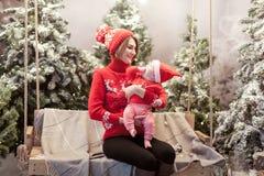 De gelukkige familiemoeder en de kindjongen in santahoed dichtbij sneeuw behandelden Kerstbomen met het zitten op schommeling Hel Stock Afbeeldingen