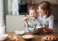 De gelukkige de familiemoeder en zoon bakken het kneden deeg in keuken stock foto