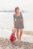 De gelukkige familiemoeder met babyzoon zit door overzees strand Royalty-vrije Stock Afbeelding